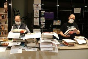 Imagen de dos empleados de La Llar del Llibre de Sabadell preparando pedidos para entregar a los hogares.