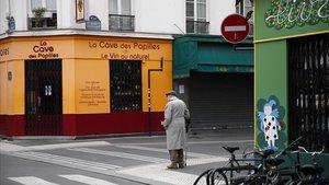 Un hombre camina por una calle desierta y con comercios cerrados en París.