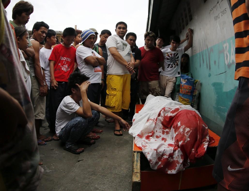 Un grupo de familiares permanece junto al cuerpo de un supuesto drogadicto asesinado durante una operación policial contra las drogas ilegales al interior de una mezquita en Manila.