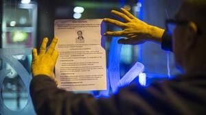 El padre colgando uno de los carteles con los que denunció en el instituto el caso de su hijo.