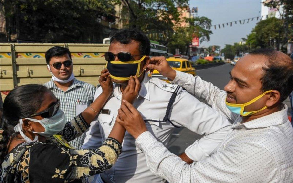 Personas en la India se protegen del coronavirus con mascarillas.