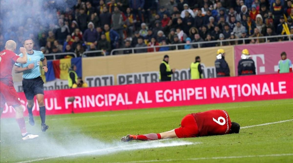 Lewandowski, en el césped tras caer un petardo a su lado en el Rumanía-Polonia.