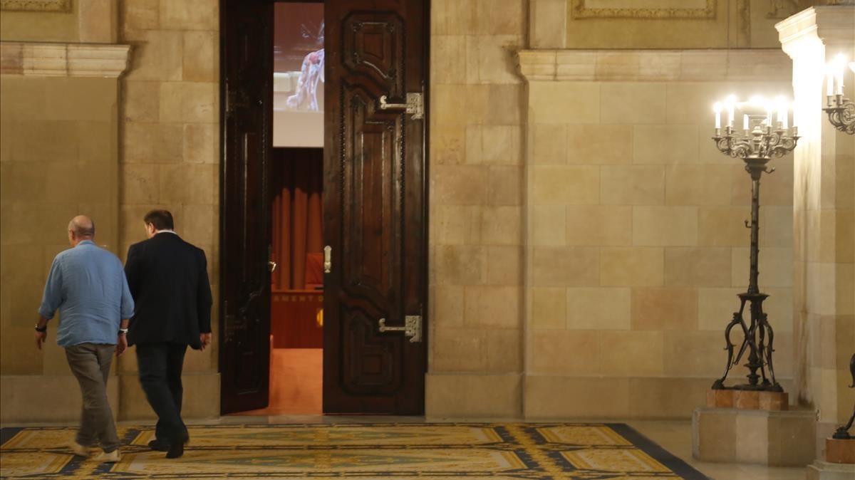 Lluís Llach y Oriol Junqueras abandonan el hemiciclo durante un receso.