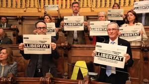 Los concejales del PDECat en Barcelona muestran carteles pidiendo la libertad de los encarcelados. Con un lazo amarillo, el lugar que ocupaba el exedil y 'exconseller' Joaquim Forn.