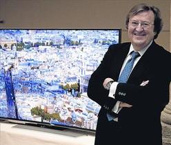 Luis Sahún, director general de Astra en España, junto a un televisor 4K.