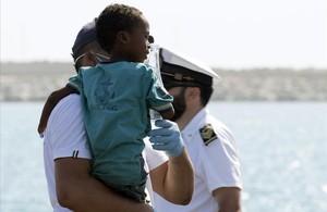 Un medico tiene en brazo un niño desembarcado del barco de la Guardia de Finanza en Pozzallo, Sicilia