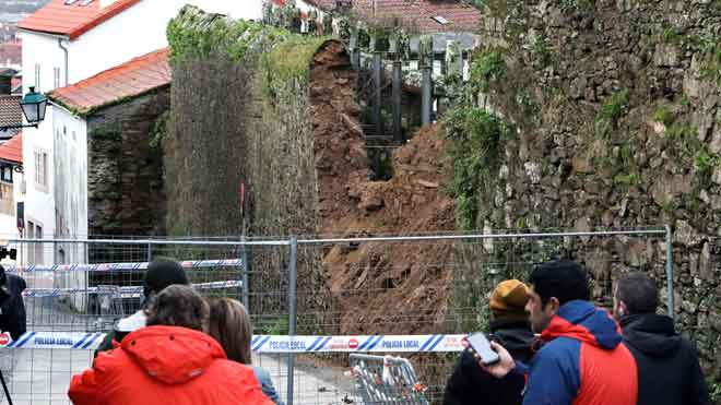 Muere un hombre al caerle encima en Santiago un muro que derrumbó el temporal. En la foto, curiosos se acercan a ver la pared que cayó.