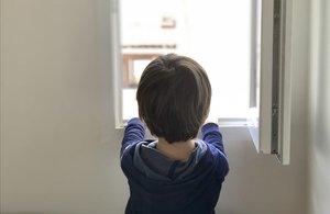 Un niño de cinco añosmira por la ventana de su casa en Madrid, de la que no sale desde el pasado 11 de marzo.