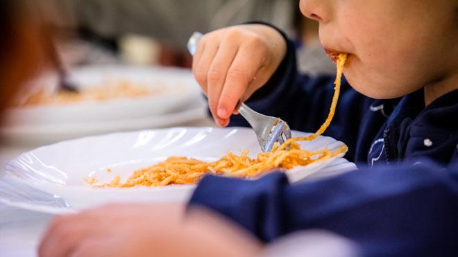 Preparación de un menú en la escuela Dovella, centro que participa en la prueba piloto de ofrecer menos carne roja y más proteína vegetal. En la foto, un niño en la hora del comedor en la escuela.