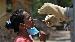 Un sanitario realiza la prueba del covid-19 a una mujer en Kolkata (India).