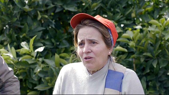 Una jornalera andaluza junto al naranjal