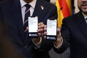 Torrent y Aragonès muestran el proyecto de los Presupuestos en sus móviles.