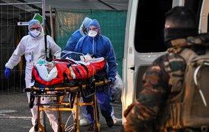 Traslado de un paciente con coronavirus desde un hospital militar a un ambulancia en Mulhouse, Francia.