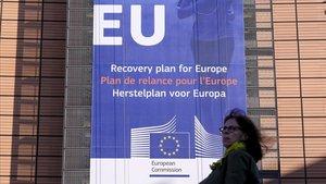 Una mujer camina ante un anuncio del plan de recuperación impulsado por la Comisión, en la fachada del edificio del Ejecutivo comunitario.