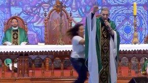 Una mujer tira al suelo a un sacerdote en plena misa