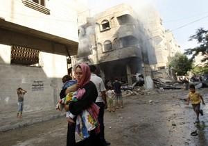 Una mujer palestina corre con su hijo para resguardarse de los ataques israelís, este jueves en Gaza.