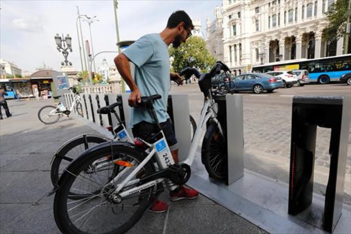 Un usuario del BiciMad se dispone a coger una bicicleta en el centro de Madrid.