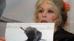 La actriz Brigitte Bardot enseñando una imagen donde una foca se come un bebé.