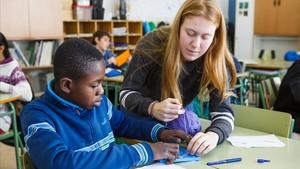La estudiante de Magisterio, Paula Gorgot, ayuda a un alumno de sexto de primaria del colegio Doctor Salarich, en Vic, la semana pasada.