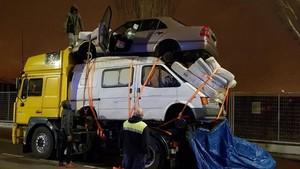 Un camió circula carregat amb una furgoneta, un cotxe i 4 matalassos