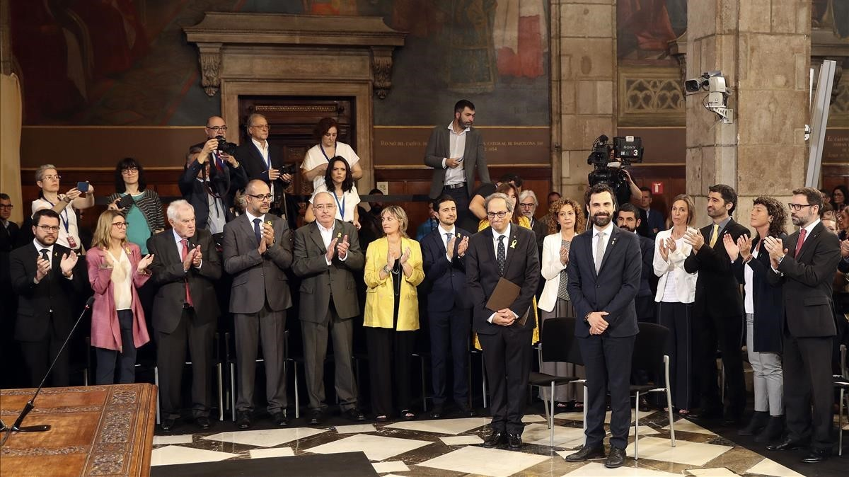 El presidente de la Generalitat, Quim Torra, y el del Parlament,Roger Torrent,reciben el aplauso de los nuevos 'consellers'.