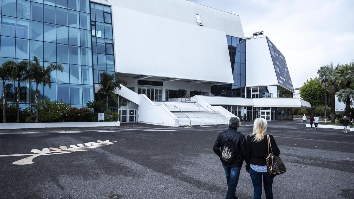 Dos personas pasean, el lunes, frente al Palacio de Festivales de Cannes.