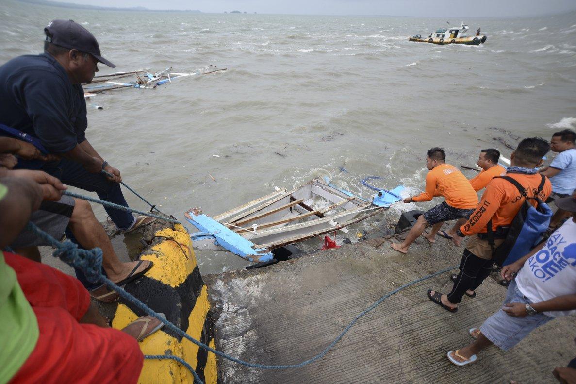 Miembros de la Guardia Costera de Filipinas transportan los restos de un barco.