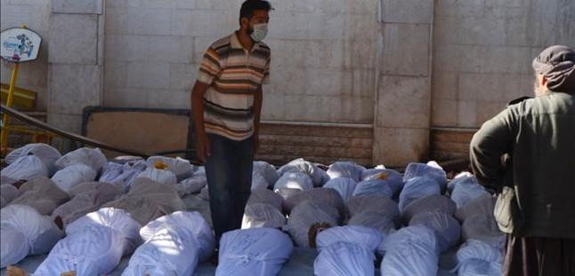 Un activista sirio inspecciona los cuerpos de decenas de muertos en el ataque, en la región de Guta.