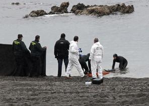 Agents de la Guàrdia Civil retiren el cos del subsaharià trobat avui a la platja del Tarajal de Ceuta.