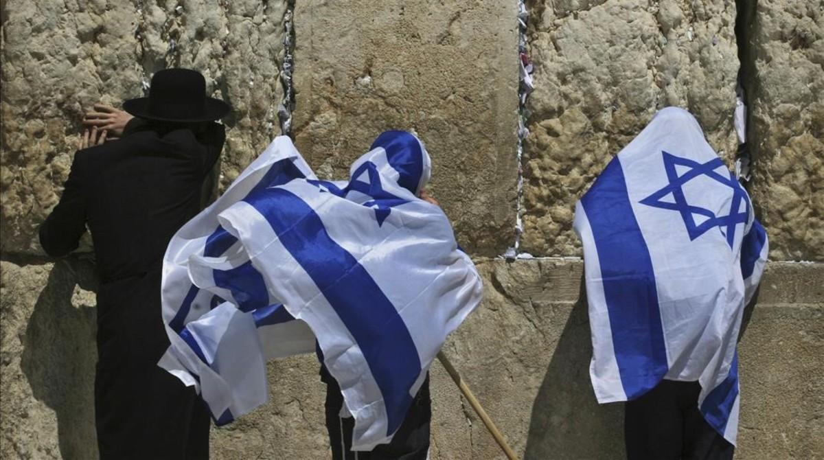 Jóvenes israelís se cubren con la bandera de Israel junto a un untraortodoxo frente al Muro de las Lamentaciones.