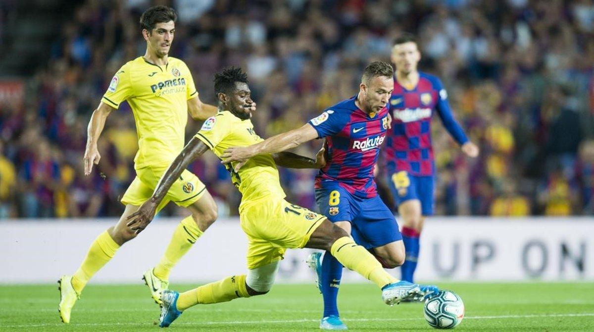 Arthur protege el balón del acoso de Anguissadurante el partido de Liga entre el FC Barcelona y el Villarreal