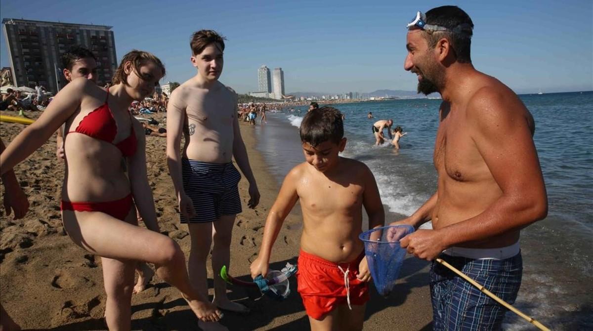 Bañistas con unas medusas recién pescadas en la playa de la Barceloneta, este lunes.