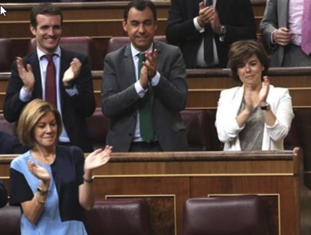 Pablo Casado, María Dolores de Cospedal y Soraya Sáenz de Santamaría, en el pleno de este martes en el Congreso, aplauden al portavoz del grupo del PP, Rafa Hernando.