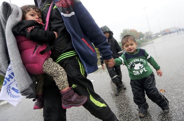 Un hombre camina llevando a dos niños bajo la lluvia junto a la frontera con Eslovenia.