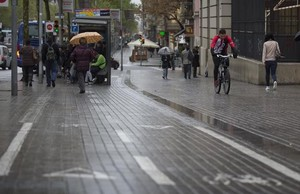 Un ciclista sortea una parada de bus instalada sobre el carril bus, en Gran Via.