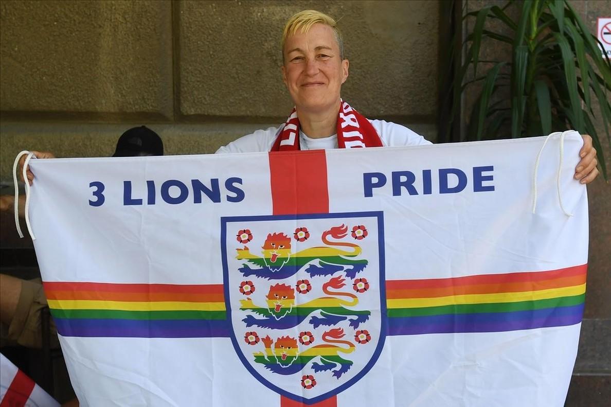 Din Cunningham sostiene una bandera inglesa, coloreada con el arco iris, el símbolo de la comunidad LGTB, en Volvogrado