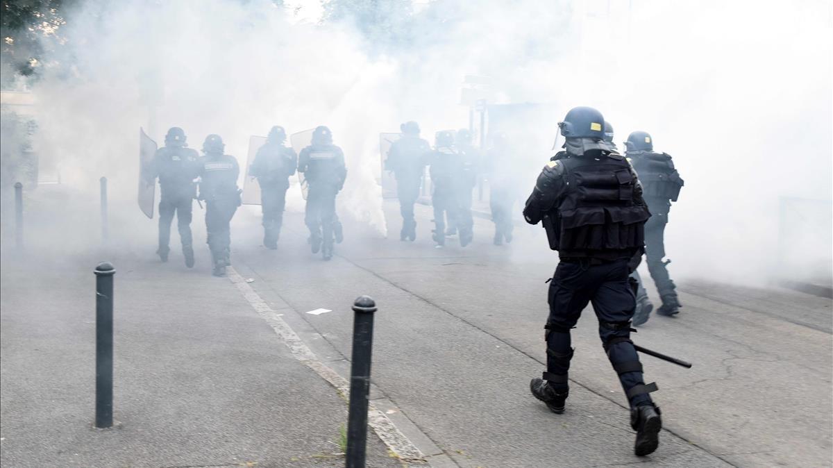 La policía carga contra los manifestantes en medio de una nube de gases lacrimógenos.