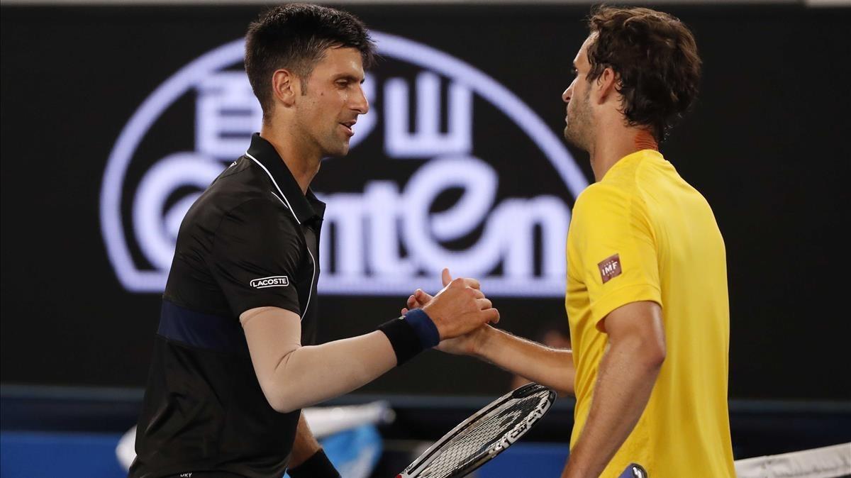 Djokovic recibe la felicitación de Ramos tras su partido de tercera ronda en Melbourne.