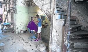 LA CIUDAD DESCONCHADA. Los habaneros se han tenido que adaptar al deterioro del entorno: este joven ha instalado unapeluquería en la caja de la escalera del que antaño fue un lujoso edificio.