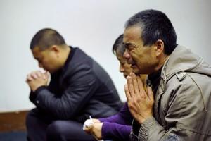 Familiares de los pasajeros del vuelo de Malaysia Airlines rezan, en un hotel de Pekín.