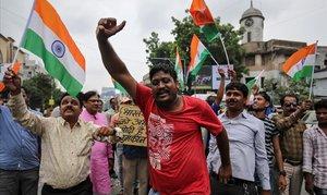 La gente grita consignas mientras celebran después de que el gobierno indio eliminó el estado especial de Cachemira en Ahmedabad, India