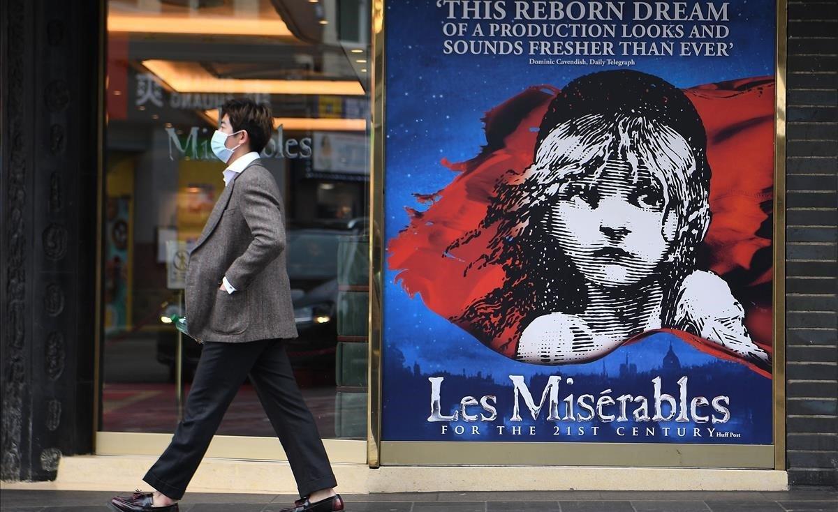 Un hombre con mascarilla pasa junto a la entrada de un teatro cerrado en Londres.