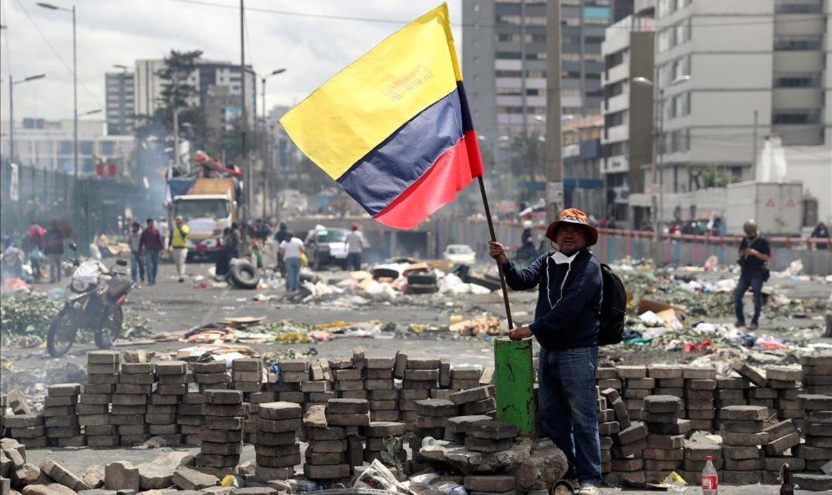 Un hombre sostiene una bandera ecuatoriana tras una protesta por las calles deQuito.