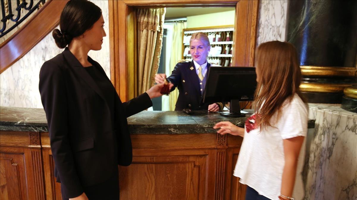 La recepcionista de un hotel de Barcelona atiende a una clienta.