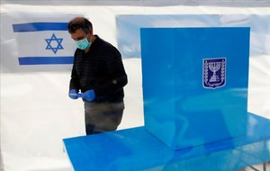 Un israelí vota protegido por mascarilla por la amenaza del coronavirus.