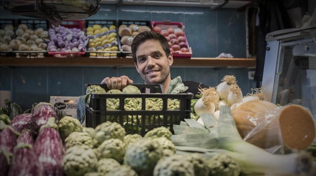 David muestra las alcachofas que vende en el mercado de Fort Pienc