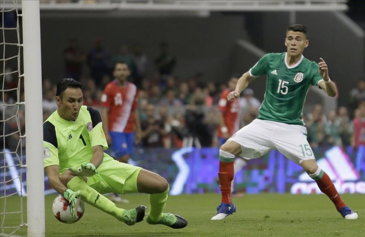 Keylor Navas ayuda a introducir en su portería el balón rematado por el mexicano Araujo.