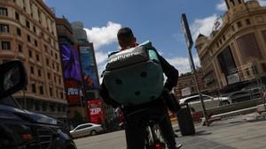 Un 'rider'de Deliveroo realizando su repartoen su bicicleta.