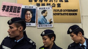 Unos policías frente a las fotos de Gui Minhai (izquierda) y otro de los cinco libreros,Yau Wentian, que fue condenado a 10 años de prisión en el 2015.