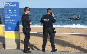 Los Mossos cierran la platja de Sant Sebastià mientras la Guardia Civil inspecciona la zona.